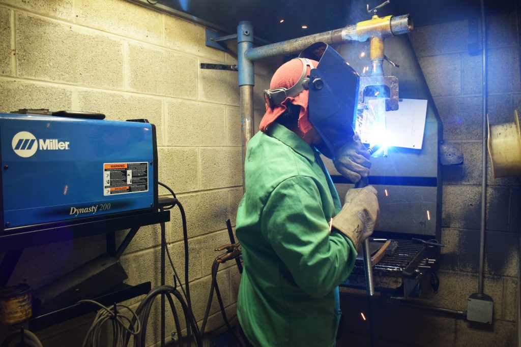 A Middle College manufacturing student welding