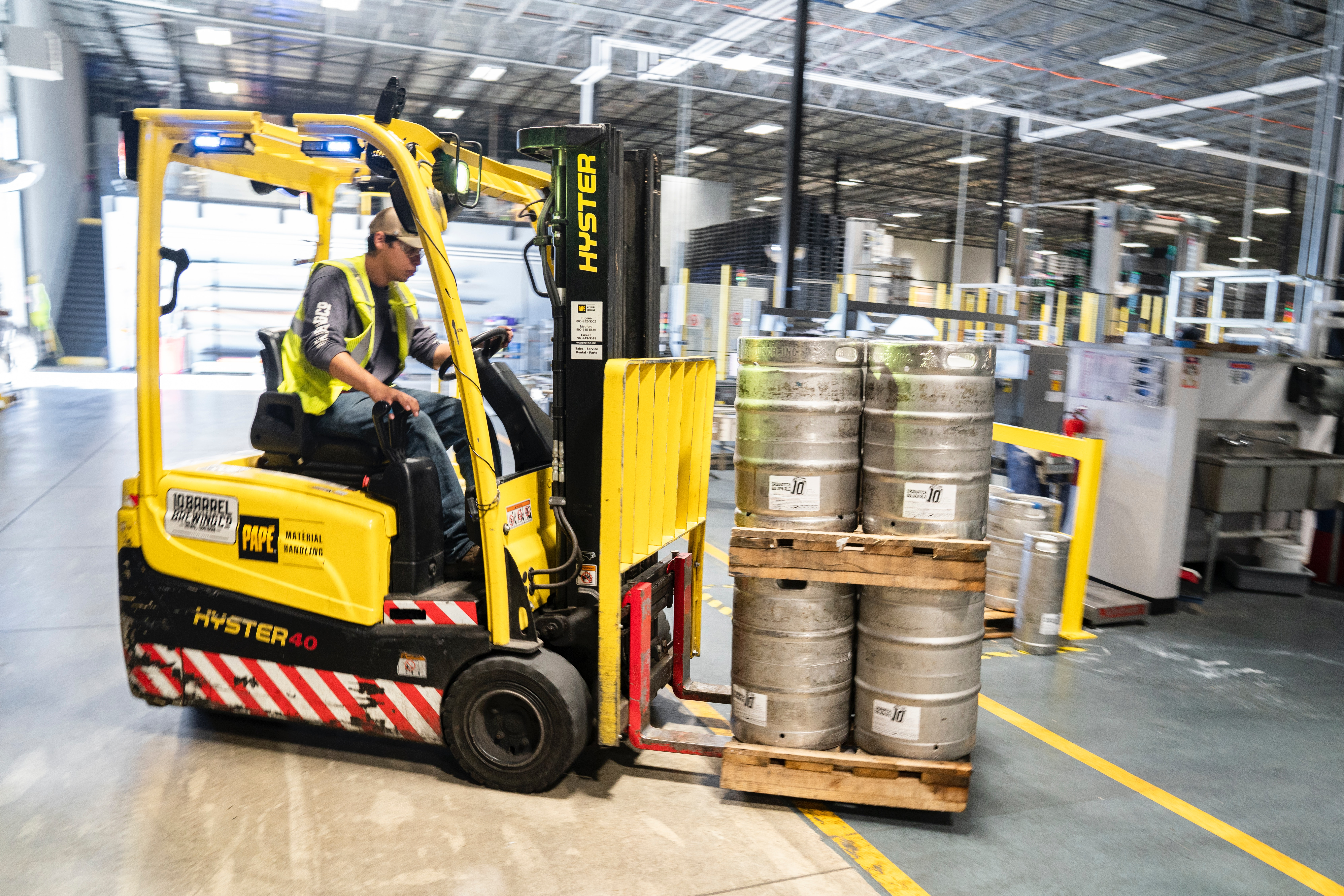 Forklift carrying metal barrels in manufacturing facility