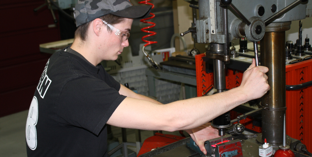 Middle College manufacturing student working on a drill press