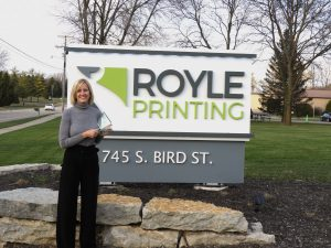 Dawn recieves the Champions in Action Award by the Royle Printing sign