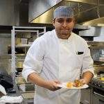 A Middle College student prepares a meal in the kitchens at Madison College