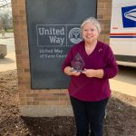 Ann receives the Champions in Action Award by the United Way sign