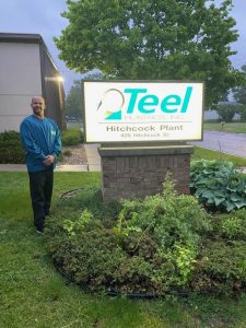 Nathan, WIOA Dislocated Worker Program participant, stands next to Teel Plastics sign.