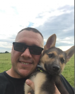 Thomas, a Windows to Work participant, poses with his German Shepherd puppy.